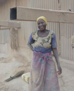Afbeelding: Woman at work at rice husk machine at Nduta